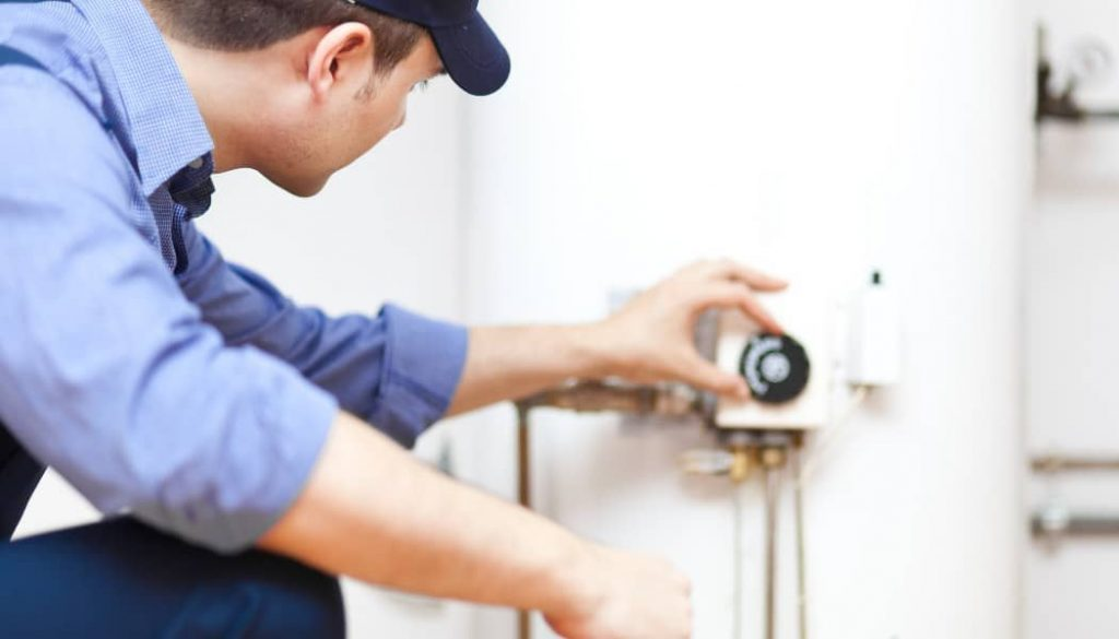 plumber-with blue-dress-fixing-a-water-heater