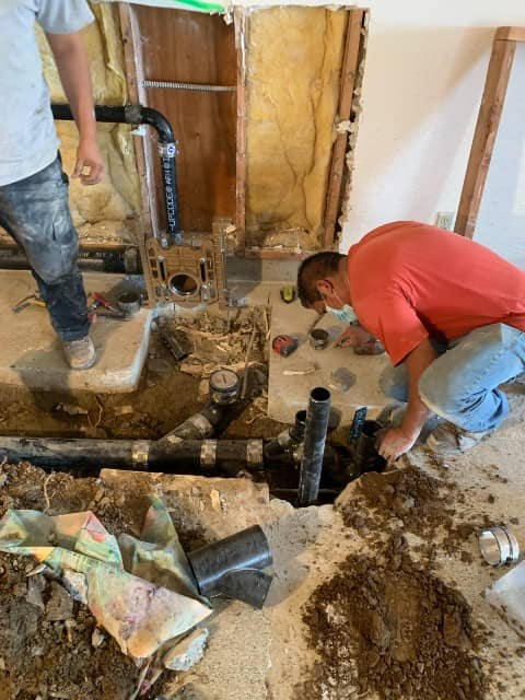 Plumbing-contractor-with-red-shirt-and-blue-pans-repairing-a-pipe